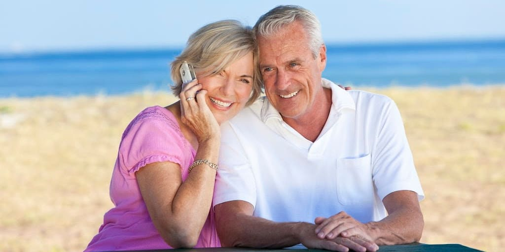 Happy snowbird  couple sitting together at a table by a beach talking on a cell phone