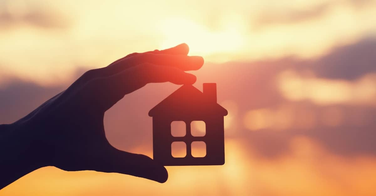 silhouette of hand holding a small house cutout against a sunset