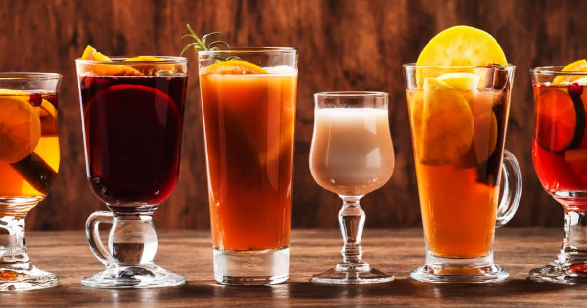 Selection of autumn hot and cold sangria drinks on wood background